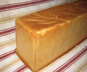 A loaf of bread made in a bread pan to be cut into slices, like a sliced bread puzzle