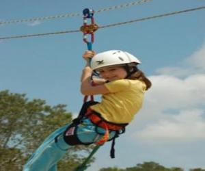 Adventurous girl jumping with a rope and harness puzzle