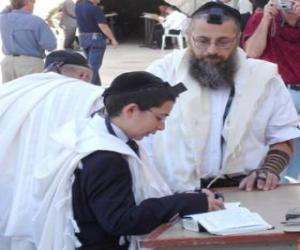 Boy studying with his teacher, both with Kippah, ritual small skullcap puzzle