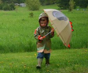 Boy with his umbrella and rain jacket under the spring rain puzzle
