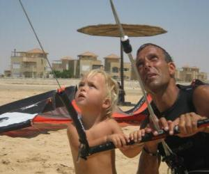 Child doing flying a kite with his father puzzle