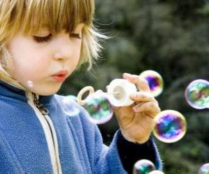 Child playing to blow soap bubbles puzzle