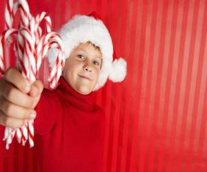 Child with hat of Santa Claus and candy canes in hand puzzle