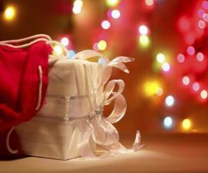 Christmas gift wrapped in white paper and decorated with a bow puzzle