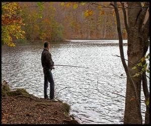 Fishing - Fisherman in river action in a forested landscape puzzle