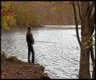 Fishing - Fisherman in river action in a forested landscape