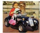 Girl on a classic toy car