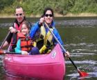Family, father, mother and daughter, sailing and paddling a canoe, equipped with life vests