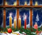 Christmas candles lit in front of a window