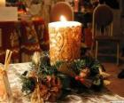 Candle ignited as a centerpiece adorned with sprigs of holly and fir