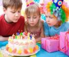 Girl in the moment of blowing out the candles on her birthday cake