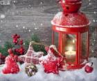 Christmas lamp with burning candle and holly decorations