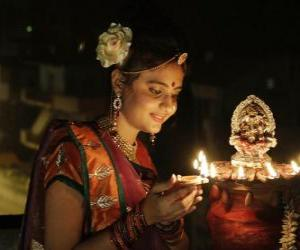 Woman kneeling with an oil lamp in hers hand in the celebration of Diwali puzzle